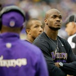 In this Dec. 29, 2013, file photo, Minnesota Vikings running back Adrian Peterson stands on the sidelines during the first half of an NFL football game against the Detroit Lions in Minneapolis. After a day of public pressure from angry fans and concerned sponsors, the Vikings have placed star Peterson on the exempt-commissioner's permission list, which will require him to stay away from the team while he addresses child abuse charges in Texas.