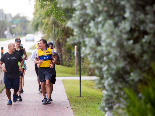 With a group of runners in tow retired firefighter Jack Bills, right, runs past Vanderbilt Beach parking garage as he raises awareness for fallen first responders and the annual Brotherhood ride Saturday, July 1, 2017 in Naples. The annual Brotherhood ride takes place later this month.