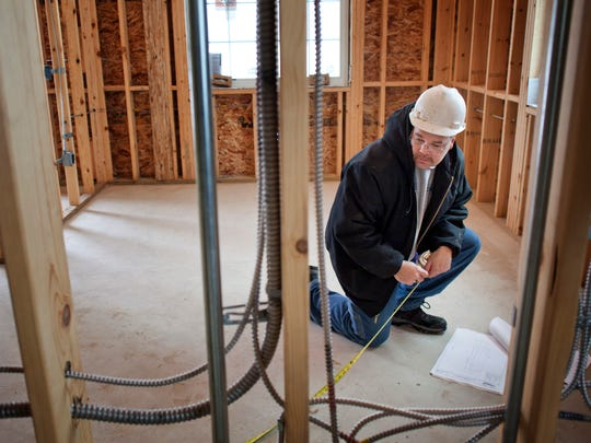 Subcontractor Craig Senyk takes measurements for installing cabinets and counter tops Wednesday at the site of the new Township Hall in Fort Gratiot.