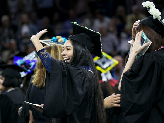 Samantha Garcia waves to friends and family at her graduation from FGCU on Saturday.