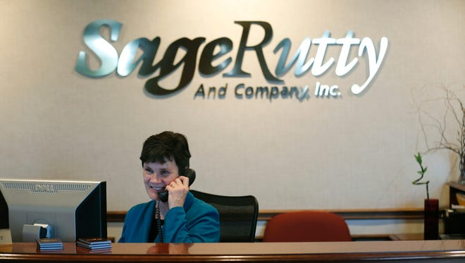 """Debbie Pelcher takes phone calls at the front desk of Sage Rutty. The company was named """"Top Workplace"""" in the Small Business category this year. The 101-year-old local company is involved in financial planning/investments."""