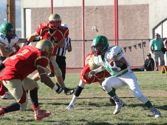 Farmington running back Donovan Gonzalez (28) carries the ball against Española Valley during a first round game of the 5A football playoffs on Saturday in Española Valley.