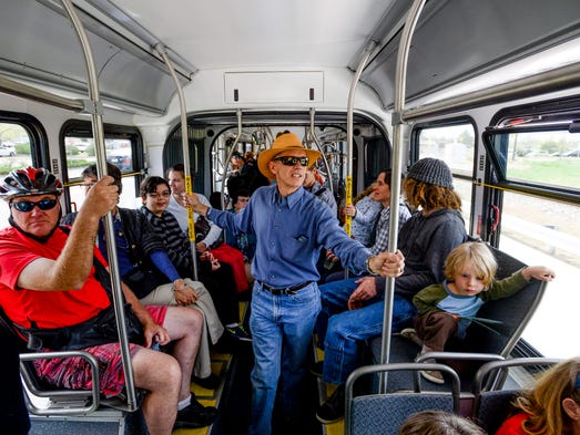 Mark Imhoff, center, takes a ride on the first MAX bus to leave the station Saturday, May 10, 2014, in Fort Collins. Hundreds of people gathered to celebrate the opening, ride the buses and participate in activities at various stops.