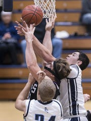 Redwood's Drew Stogsdill, Mission Oak's Richard Torrez and Redwood's Andres Solis collide under the basket for a rebound in a non-league high school boys basketball game Tuesday, December 6, 2016.