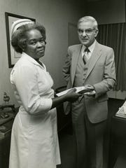 Orthopedics nurse Ella Edwards receives TMH's first Employee of the Month award in 1980 from hospital administrator M.T. Mustian, who died Wednesday. Mustian oversaw the integration of TMH in 1971.