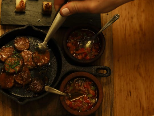 A tourist serves himself chorizo, the local sausage, at a dinner at The Argentine Experience in Buenos Aires, Argentina.