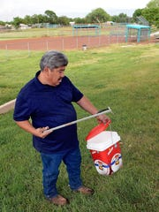 Hector Aguilar uses a claw grabber extension to remove a hypodermic needle from one of the baseball fields at Atrisco Park in Albuquerque, N.M.