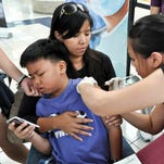 Kristan Ayson, 9, left, sits on the lap of his mother, Elvira Ayson, and averts his attention to a mobile phone as he is given an influenza vaccination by registered nurse Eizabeth Santos at the Guam Medical Association health fair outreach at the Micronesia Mall in Dededo on Feb. 9, 2013.