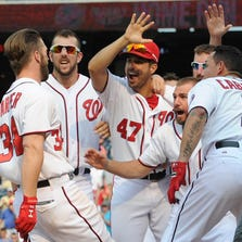 Aug 7, 2014; Washington, DC, USA; Washington Nationals left fielder Bryce Harper (34) is greeted by teammates after hitting the game-winning home run in the 13th against the Mets at Nationals Park. Mandatory Credit: H.Darr Beiser-USA TODAY Sports