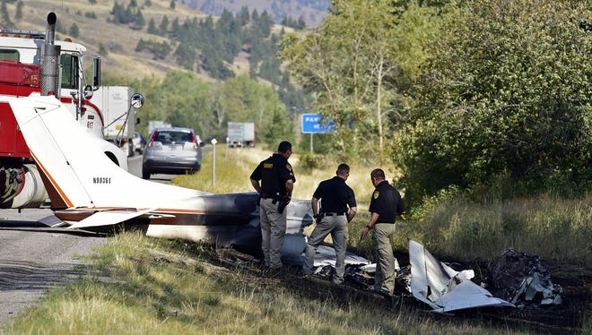 """Missoula County sheriff's deputies look at the wreckage of a Cessna 182 that crashed on the shoulder of Interstate 90 near Rock Creekont., on Sunday, Aug. 28, 2016. The crash killed 52-year-old Darrell Ward of Deer Lodge, a star of the History channel series """"Ice Road Truckers"""" and pilot Mark Melotz, 56, of Arlee. Ward was returning to Montana to film a pilot episode of a documentary-type series about the recovery of plane wrecks."""