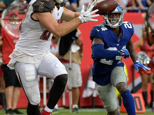 Tampa Bay Buccaneers tight end Cameron Brate (84) catches a 14-yard touchdown pass in front of New York Giants cornerback Eli Apple (24) during the fourth quarter of an NFL football game Sunday, Oct. 1, 2017, in Tampa, Fla. (AP Photo/Phelan Ebenhack)