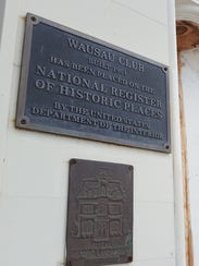 Plaques outside the Wausau Club show it's a designated