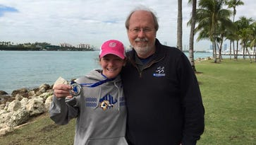 Becca Pizzi, left, and Mars Hill University Cross Country Coach Mike Owens, celebrate Pizzi's Miami win during the World Marathon Challenge