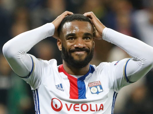 FILE - This is a Thursday, May 11, 2017 file photo, of Lyon's Alexandre Lacazette  as he grabs his head after teammate Fakir missed a chance to score during the second leg semi final soccer match between Olympique Lyon and Ajax in the Stade de Lyon,  Decines, France. Atletico Madrid's transfer ban was upheld by the Court of Arbitration for Sport on Thursday June 1, 2017, harming Manchester United's hopes of signing Antoine Griezmann. The FIFA ban prevents Atletico from registering new players until January. Atletico had lined up Lyon forward Alexandre Lacazette as a potential replacement for Griezmann.(AP Photo/Laurent Cipriani/File)