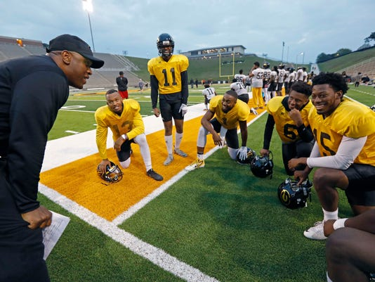 Grambling's quarterback coach Kendrick Nord, left, jokes with offensive players including quarterback Devante Kincade (1) middle and wide receiver Quintin Guice (13) second from left, during a break at practice, Thursday, Nov. 16, 2017, at Eddie G. Robinson Memorial Stadium in Grambling, La. Kincade, who played two seasons at Ole Miss, says playing football at a Historically Black College or University is an experience to savor. Playing at an HBCU is not just about entertaining halftime shows the schools are known for, it's about community. (AP Photo/Rogelio V. Solis)