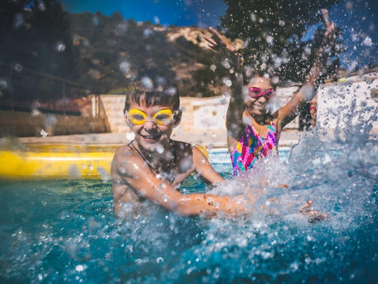 Young boy and girl having fun splashing water in swimming pool