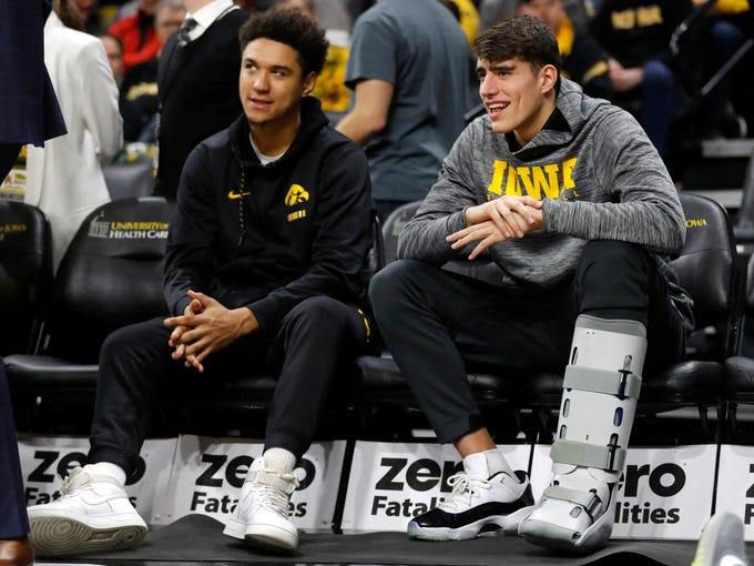 Injured Iowa players Cordell Pemsl, left, and Luka Garza sit on the bench during the second half of an NCAA college basketball game against Savannah State, Saturday, Dec. 22, 2018, in Iowa City, Iowa. (AP Photo/Charlie Neibergall)