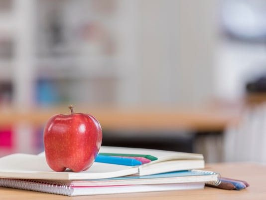 Red delicious apple on top of books in classroom