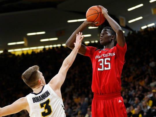 Rutgers forward Issa Thiam (35) shoots a 3-point basket over Iowa guard Jordan Bohannon during the first half
