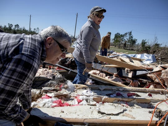 In this March 5, 2019 file photo, Cindy Sanford, center, sifts through the debris with help from her brother, Tim Lancaster, left, and stepfather, Michael Boutwell, while retrieving personal items after a tornado destroyed her home in Beauregard, Ala. The Alabama community hit by a killer tornado worked for months without success to build a storm shelter before the twister struck.