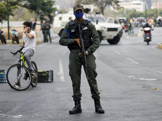 A soldier stands on an avenue leading to La Carlota air base in Caracas, Venezuela, Tuesday, April 30, 2019.