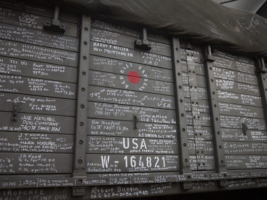 In this photo taken on Thursday, Nov. 7, 2019, names of veterans who have visited are written on the side of the U.S. Army truck, The Red Ball Express, at the Remember Museum 39-45 in Thimister-Clermont, Belgium. Countless veterans have written their names on the sides of the truck, but as the owners of these white signatures die off it will be up to the next generation to remember their sacrifices. Veterans of the WWII Battle of the Bulge are heading back to mark, perhaps the greatest battle in U.S. military history, when 75-years ago Hitler launched a desperate attack deep through the front lines in Belgium and Luxembourg to be thwarted by U.S. forces. (AP Photo/Virginia Mayo)