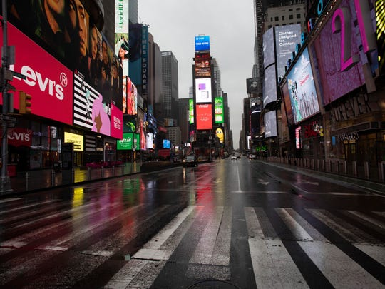 Times Square is mostly empty Monday in New York. Gov. Andrew Cuomo has ordered most New Yorkers to stay home from work to slow the coronavirus pandemic.