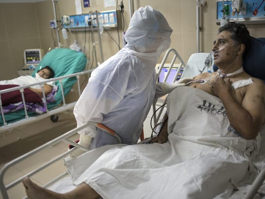 Dr. Rosa Lopez comforts her colleague Victor Cuba, an emergency room nurse infected with COVID-19, inside the Guillermo Almenara hospital in Lima, Peru, on Friday. Despite strict measures to control the virus, this South American nation of 32 million has become one of the countries worst hit by the disease.