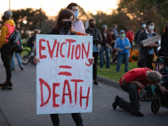 Housing activists gather in front of Gov. Charlie Baker's house Wednesday in Swampscott, Mass.