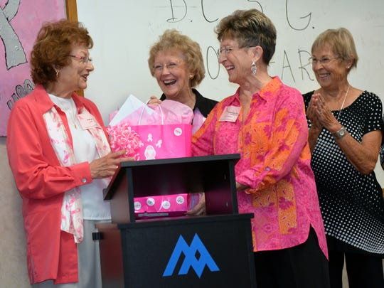 From left to right, Lori LaPlanche, a co-founder of the Breast Cancer Support Group, receives a surprise gift from core members and breast cancer survivors Kay Darcy, Roberta Utrecht, Marlys Kleppe.