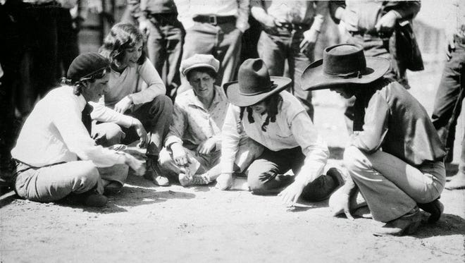 Marie Gibson, center, gambles with fellow rodeo riders. Date unknown.