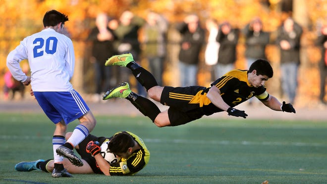 Athena's Nick Burns flies over his goal keeper Tyler Graves as Brockport's Simeon Horton applies pressure in the Class A1 final. Athena beat Brockport 2-0