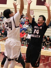 Tularosa's Ryder King tries to score in the paint while being defended by Hatch's Derek Garay.