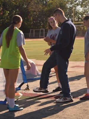 Wayne Hills players Natalia Aliotta (right) and Samantha Sklar (left) teaching Justin LaPlaca at a team practice last week.