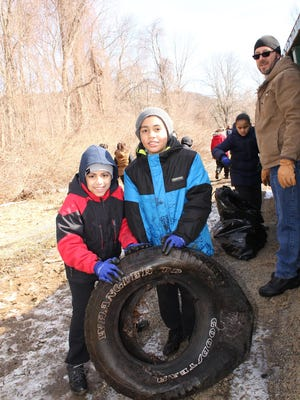 Students unearth a discarded tire while helping to clean up Waterloo Village during the NJCCC's seventh annual Environmental Student Exchange on March 19.