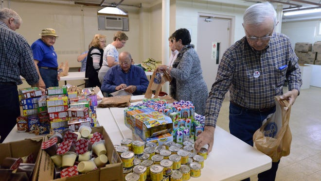 Dean Ackerman, right, and other volunteers fill up bags with breakfast items Tuesday, Nov. 7, 2017, at Bremen-Bethel Presbyterian Church in Bremen. The group bagged breakfasts for 146 students at Bremen Elementary.