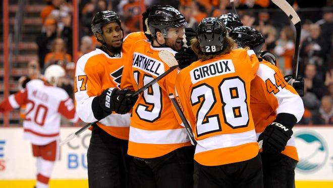 Philadelphia Flyers left wing Scott Hartnell (19) celebrates his goal with right wing Wayne Simmonds (17), center Claude Giroux (28) and defenseman Kimmo Timonen (44) against the Detroit Red Wings.