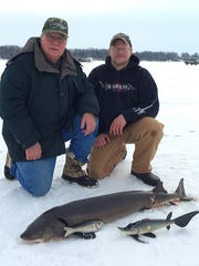 George Schmidt, left, and Mike Faskell pose with Schmidt's first sturgeon, which he speared Feb. 11 on Lake Winneconne.