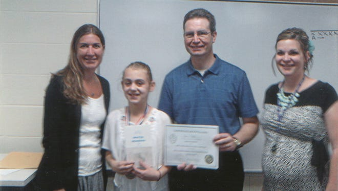 Gina Durdahl, left, presents Karin Juhl with her first place award for the Mary Jo Nettesheim Memorial Literary Competition at Chilton Middle School. Also pictured are Aaron Juhl, Karin's father and a teacher at Chilton Middle School, and Kim Tiegs, gifted and talented teacher.