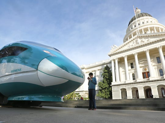 FILE - In this Feb. 26, 2015 file photo, a full-scale mock-up of a high-speed train is displayed at the Capitol in Sacramento, Calif. California high-speed rail officials are signing a contract, Tuesday, June 14, 2016, that increases the cost by $63 million and extends the deadline by 17 months for a 29-mile stretch of land in the Central Valley after ending a lawsuit that sought to block the project there. (AP Photo/Rich Pedroncelli)