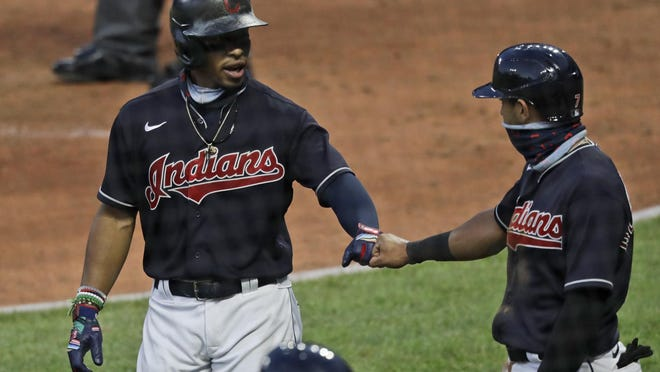 The Cleveland Indians' Francisco Lindor, left, is congratulated by Cesar Hernandez after Lindor hit a three-run home run in the fifth inning during a preseason baseball game against the Pittsburgh Pirates, Monday, July 20, 2020, in Cleveland.