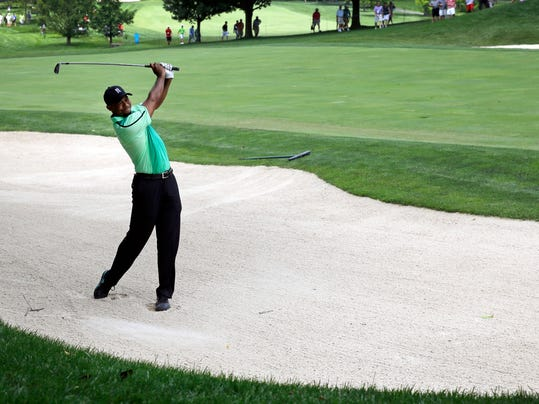 Tiger Woods chips out of a sand trap on the ninth fairway during the first round of the Quicken Loans National PGA golf tournament, Thursday, June 26, 2014, in Bethesda, Md. (AP Photo/Patrick Semansky)