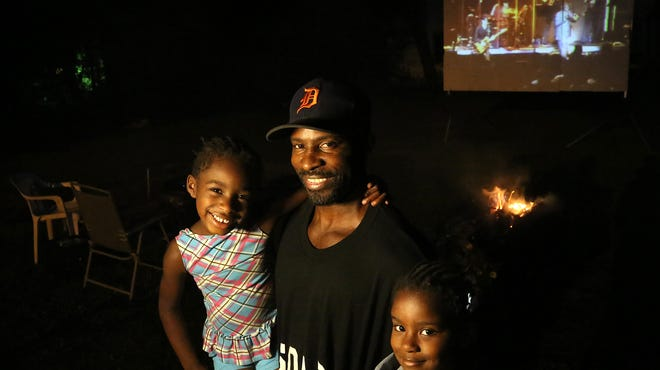 Dan Davis, 50, of Detroit with his daughters,  Dream Davis, 5, and Justice Davis, 4, during his nightly movie night at a lot next to his home on Tuesday, July 8, 2014.
