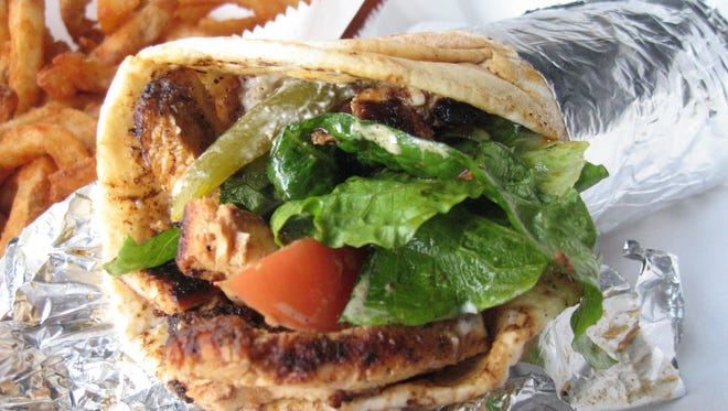 The chicken shawarma sandwich at Detroit's Bucharest Grill is made with hot-off-the-grill strips of marinated chicken, lots of pungent garlic sauce, dill pickle spears, and fresh romaine and tomato.
