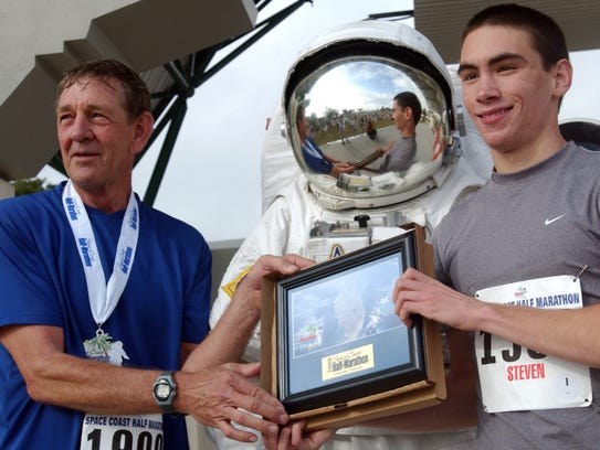Retired NASA astronaut Mike McCulley, left, hands out