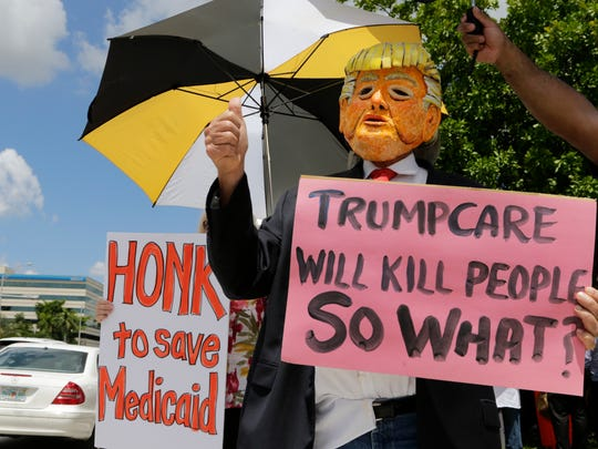 Glenn Terry, wearing a Donald Trump mask, protests agains the current GOP health care bill outside of the office of Sen. Marco Rubio, R-Fla., Wednesday, June 28, 2017, in Miami. (AP Photo/Lynne Sladky)