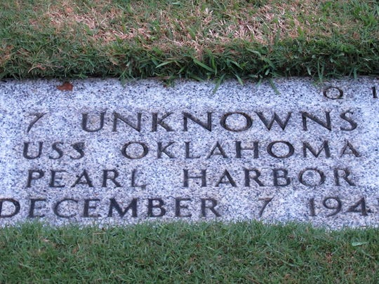 A gravestone at the National Memorial Cemetery of the Pacific in Honolulu shows a gravestone identifying it as the resting place of seven unknowns from the USS Oklahoma who died in the Japanese bombing of Pearl Harbor.