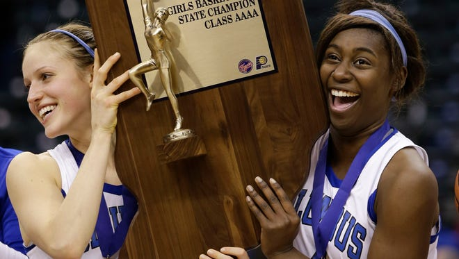 Columbus North's Ali Patberg, left, and Debie Gedeon hold up the trophy after defeating Homestead 62-56 in the Class 4A Indiana high school girls basketball state championship game in Indianapolis, Saturday, March 7, 2015.  (AP Photo/AJ Mast)