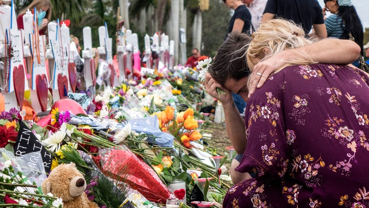 People visit a makeshift memorial in front of the Marjory