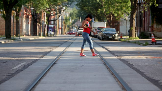 A woman crosses the completed streetcar tracks along Race Street in Over-the-Rhine. The transit authority will decide this summer who will run the operations of the circulator.